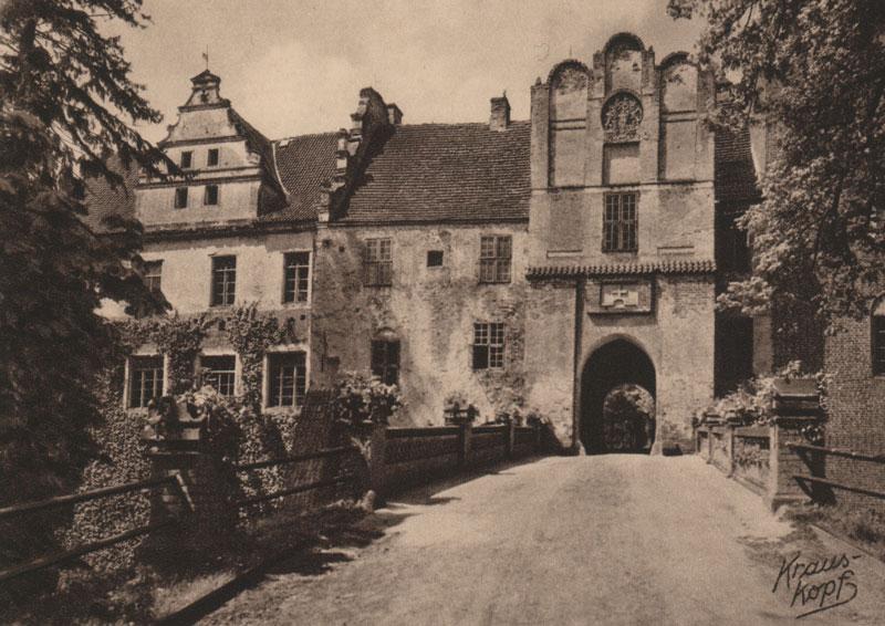 Historyczne czarno-białe zdjęcie Zamku w Szymbarku przedstawiające wejście do zamku przez arkadowy most. Na pierwszym planie widzimy drogę wiodącą przez arkadowy most do bramy wjazdowej. Most posiada kamienno-żeliwne balustrady. Na drugim planie widać budynek z przejazdem bramnym oraz po jego lewej stronie dwa budynki mieszkalne.  W dolnym prawy rogu fotografii znajduje się podpis autora zdjęcia: Krauss Kopf.