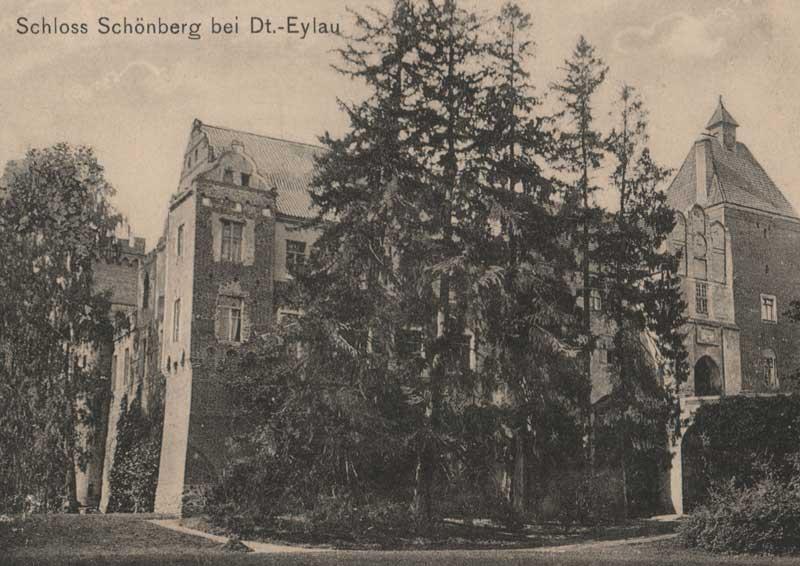 Historyczne, czarno-białe zdjęcie zamku w Szymbarku przedstawiające widok na zamek od strony mostu arkadowego. Zamek znajduje się na drugim planie, z przodu przysłaniają go wysokie drzewa iglaste, po prawej stronie fotografii widoczny jest fragment mostu arkadowego oraz przejazd bramny i kaplica zamkowa. W górnej części zdjęcia znajduje się napis: Schloss Schoeneber bei Dt.-Eylau.