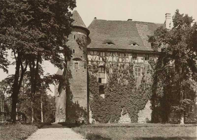 Historyczne, czarno-białe zdjęcie zamku w Szymbarku. Widok na zachodni mur zamku. Widok na dwie potężne baszty – u podstawy czworoboczne, w górnej części o kształcie walca. Widać ślad po dwóch nieukończonych nigdy basztach. Dolna część murów zamku zbudowana jest z cegły, górna część (mieszkalna) wykonana jest z muru pruskiego i zwieńczona dwuspadzistym dachem. Mur i część części mieszkalnej porośnięta jest bluszczem. Na pierwszym planie fotografii widzimy gruntową drogę prowadzącą wzdłuż murów zamku. Po lewej i prawej stronie zdjęcia widoczne są wysokie drzewa liściaste.