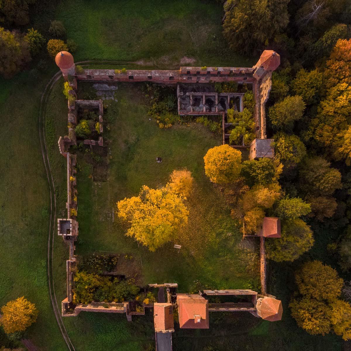 Zdjęcie współczesne ruin zamku. Widok na zamek z góry. Fotografia z drona. Zdjęcie przedstawia rzut zamku, widać na nim mury, 3 baszty, dach przejazdu bramnego, kaplicy oraz dwa drzewa na dziedzińcu i ruiny zamkowych budowli mieszkalnych. Po lewej stronie zamku widać gruntową drogę, a po prawej drzewa z zagajnika zamkowego. Zdjęcie zostało wykonane o zachodzie słońca, ma intensywną słoneczną poświatę.