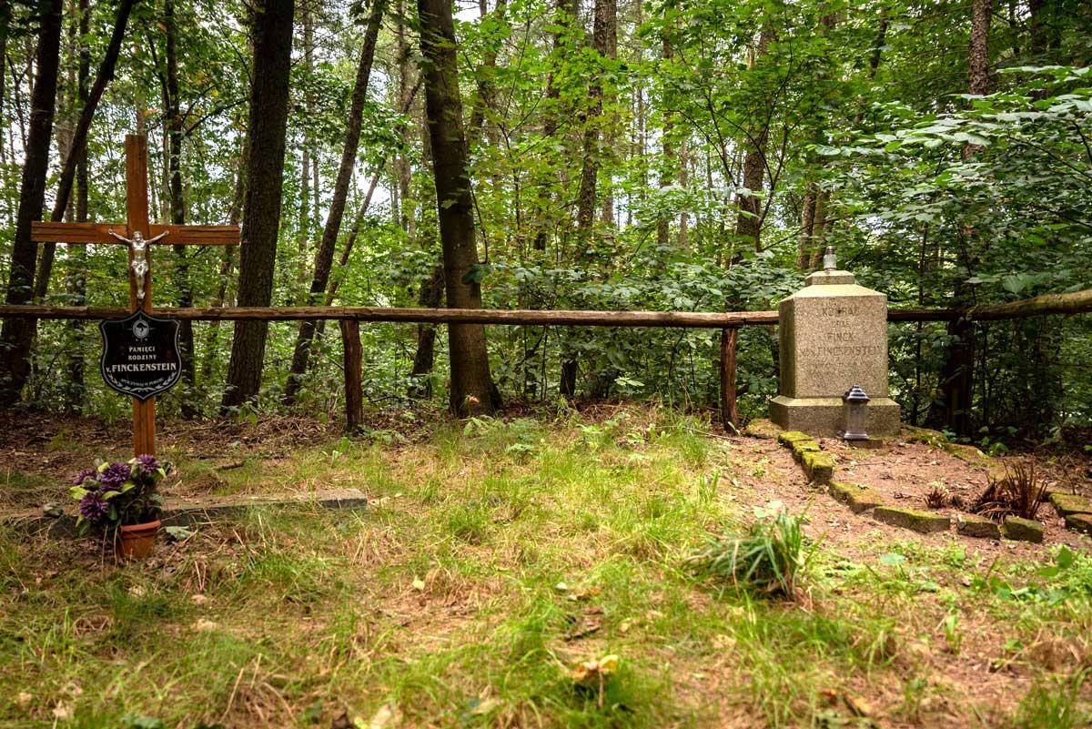 Fotografia współczesna cmentarza rodzinnego rodziny von Finkenstein, dawnych właścicieli zamku. Fotografia przedstawia ogrodzony cmentarz rodzinny. Po prawej stronie znajduje się odnowiony piaskowy sześcian na nieco szerszym postumencie. To bryła nagrobka. Przed nim z kamieni ułożono kształt symbolizujący powierzchnię grobu przed jego dewastacją. Po lewej stronie fotografii znajduje się prosty, drewniany krzyż z figurą Jezusa i tablicą informującą o poświęceniu tego miejsca pamięci rodziny von Finkenstein. Cmentarz ulokowany jest w lesie, porasta go trawa.